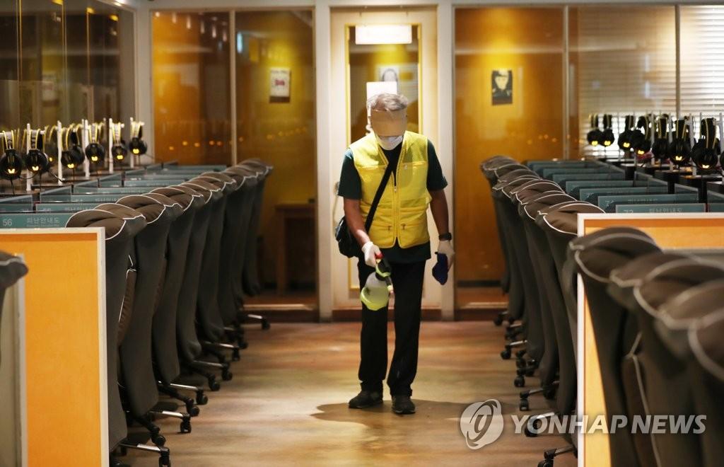 资料图片:9月10日,光州市北区一网吧,工作人员进行消毒防疫。 韩联社