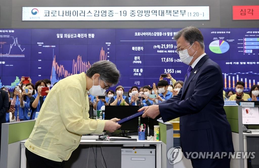 9月11日,总统文在寅(右)向新任疾病管理厅厅长郑银敬授予任命书。 韩联社
