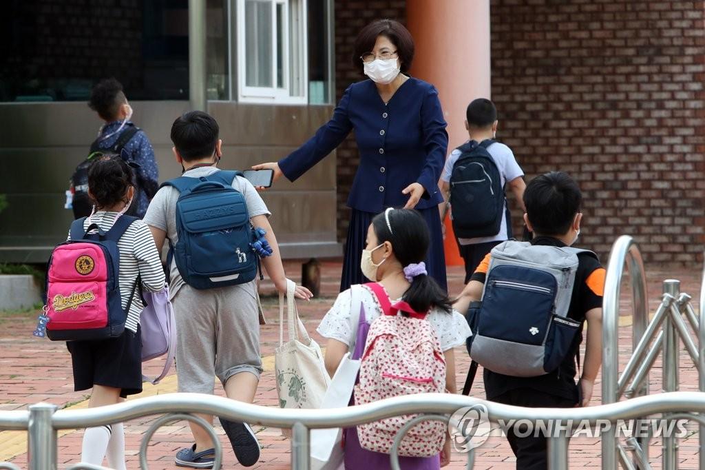 资料图片:在一所小学,老师迎接到校的学生。 韩联社