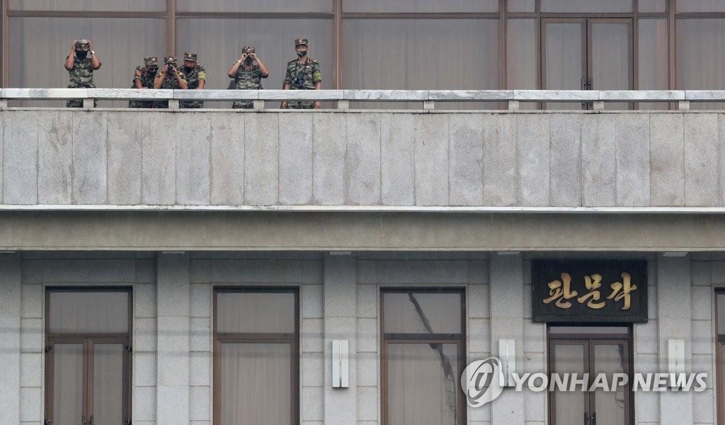 """资料图片:9月16日,在韩朝边境板门店朝方一侧的""""板门阁"""",朝鲜军人手持望远镜向韩方一侧观望。 韩联社/联合摄影团"""