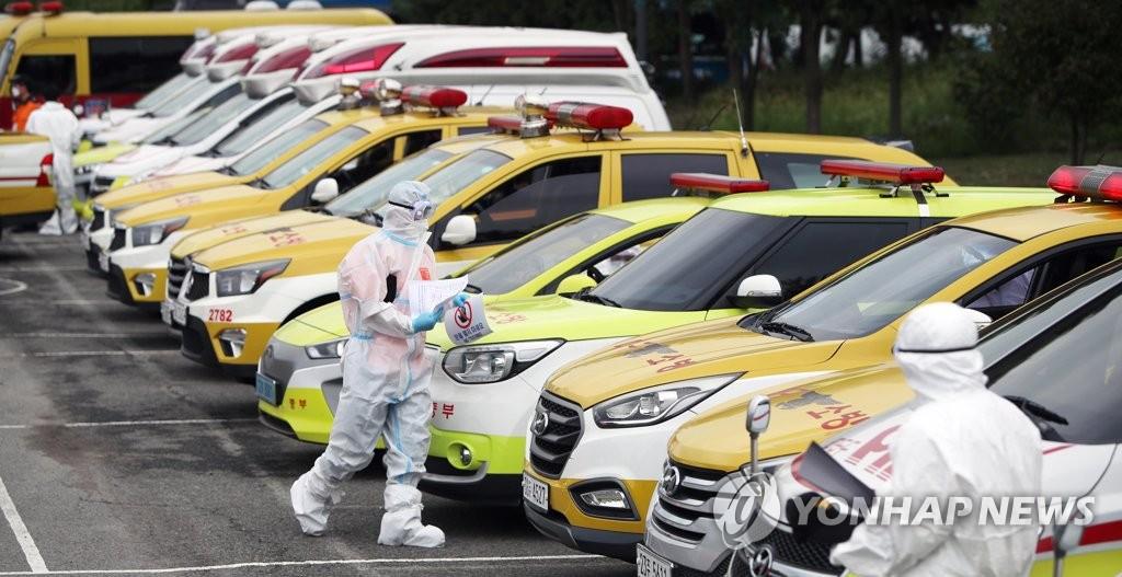 资料图片:9月16日下午,在大邱市达西区,消防队员演练移送大批新冠病人。 韩联社
