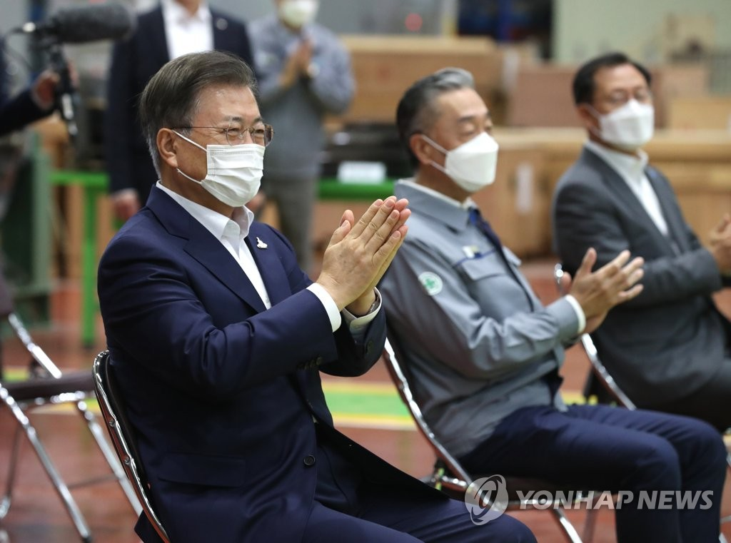 9月17日,在庆尚南道昌原市,文在寅(左一)在斗山重工听取产品介绍后鼓掌称赞。 韩联社