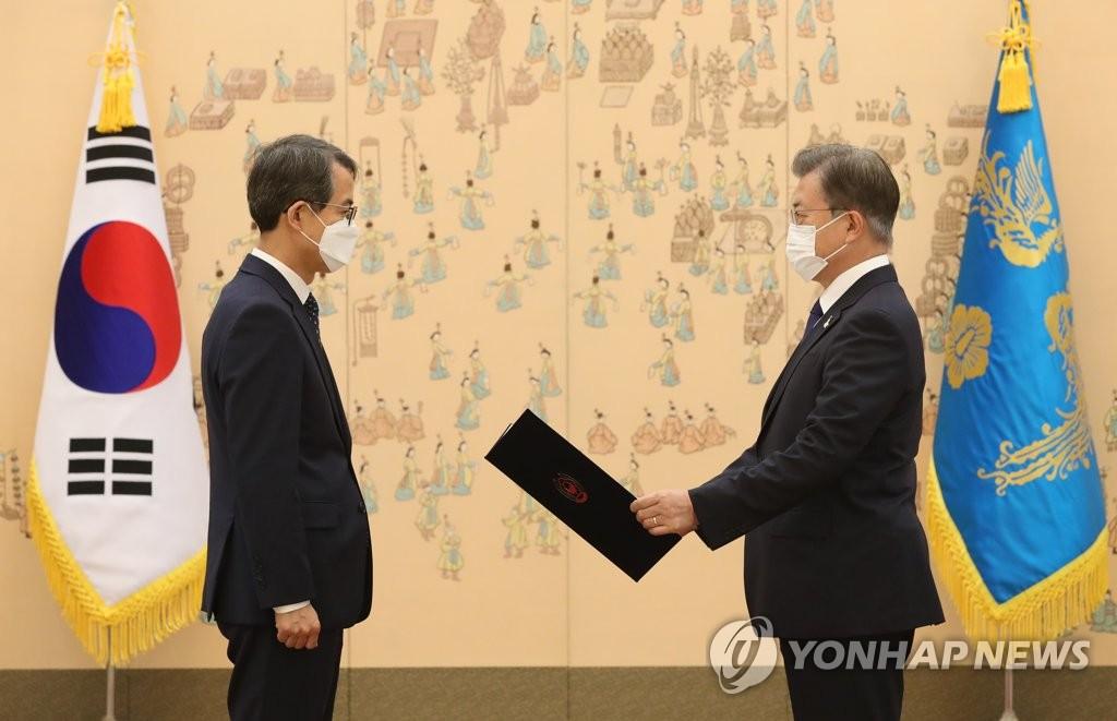 9月18日,在青瓦台,韩国总统文在寅(右)向大法官李兴九颁发任命书。 韩联社