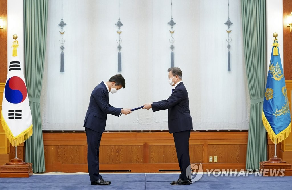 9月18日,在青瓦台,韩国总统文在寅(右)向国税厅厅长金大智颁发任命书。 韩联社