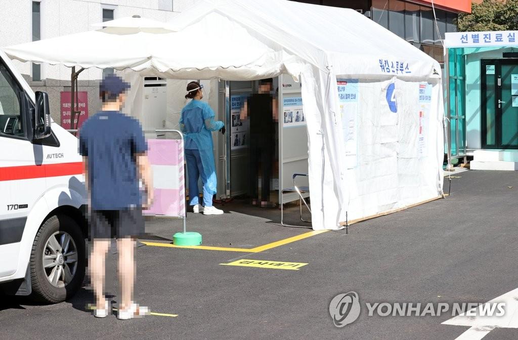 资料图片:市民在筛查诊所前待检。 韩联社