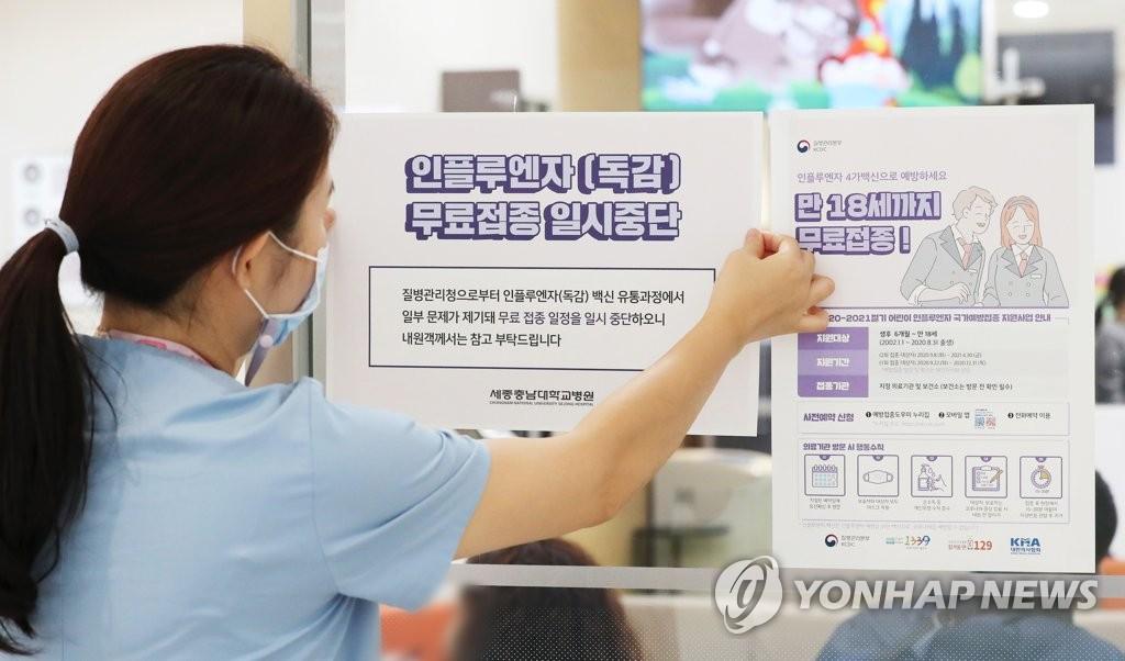 资料图片:医务人员贴出暂停流感疫苗接种的通知。 韩联社