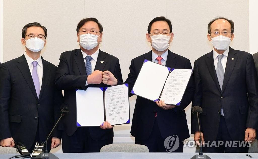 9月22日,在国会,执政党共同民主党党鞭金太年(左二)和最大在野党国民力量党鞭朱豪英(右二)就第四期补充预算案达成协议后合影。 韩联社