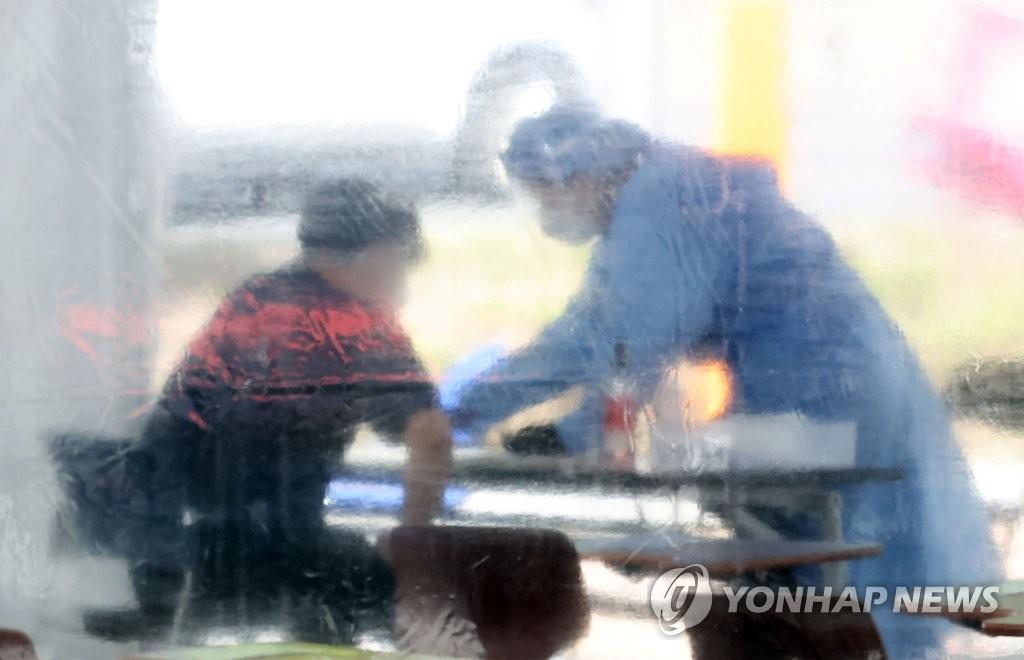 资料图片:医务工作者给市民做新冠病毒检测。 韩联社