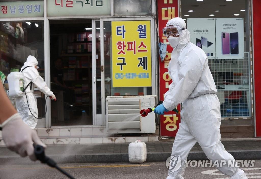 资料图片:防疫人员展开消毒防疫工作。 韩联社