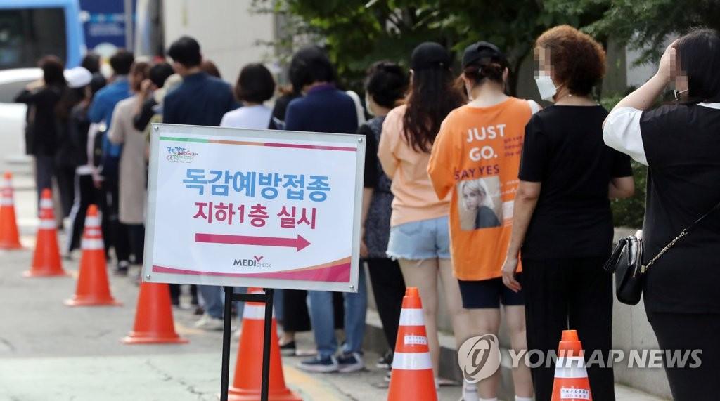 资料图片:9月25日,在韩国健康管理协会首尔西部分会健康增进医院,市民排队接种流感疫苗。 韩联社