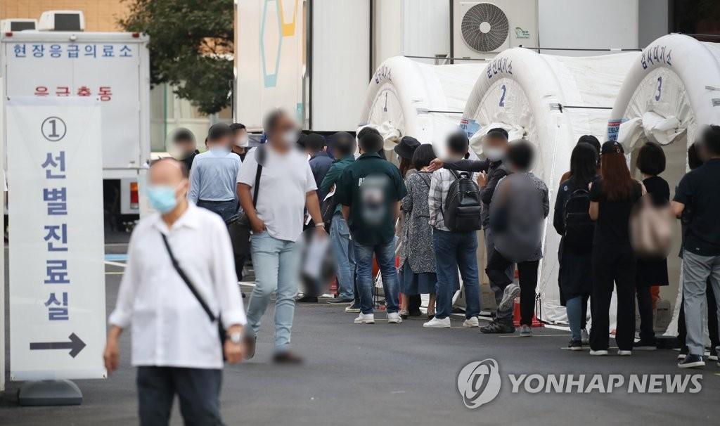 资料图片:在一处筛查诊所,市民排队候检。 韩联社