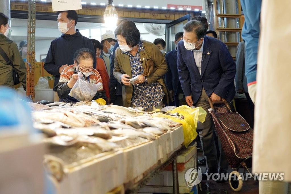 9月29日下午,在首尔市西大门区的仁王市场,韩国总统文在寅(右一)和夫人金正淑(右二)置办中秋节庆用品。 韩联社/青瓦台供图(图片严禁转载复制)
