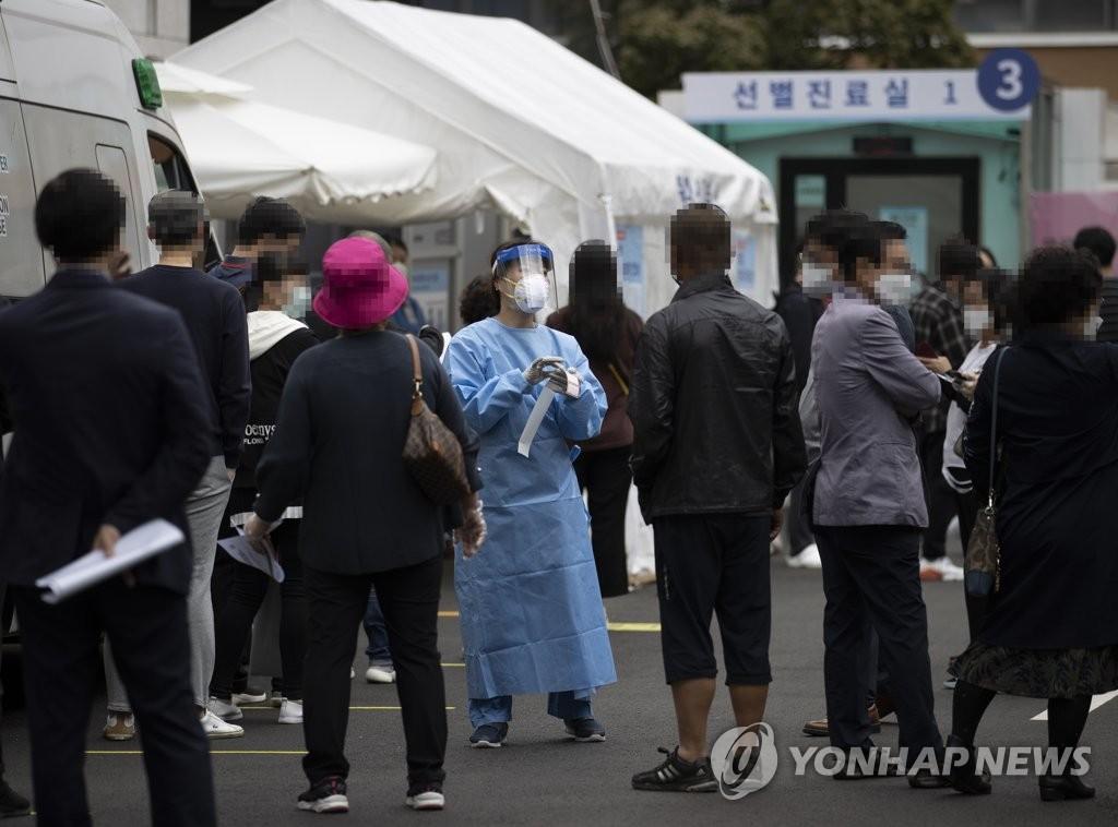资料图片:10月2日,在设于首尔国立中央医疗院的筛查诊所,众多市民前来接受新冠病毒核酸采样检测。 韩联社