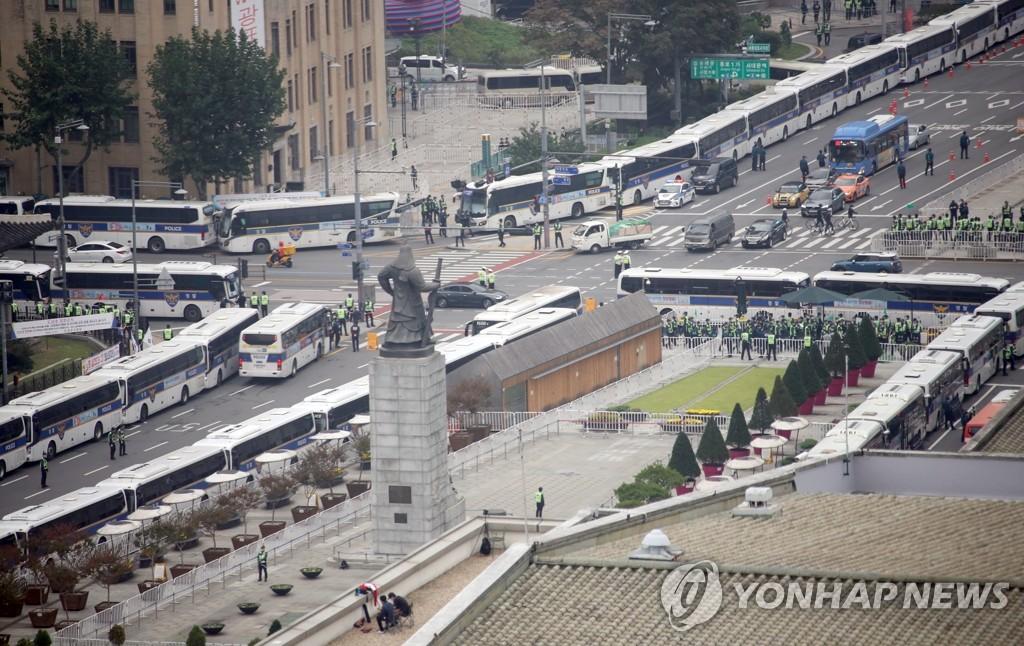 """资料图片:10月3日上午,为防止民众于""""开天节""""当天在光化门附近集会示威引发疫情反弹,众多警察大巴在路边待命。 韩联社"""