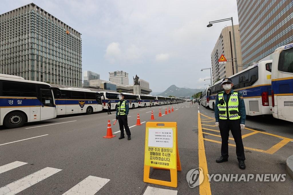 """资料图片:10月3日,在首尔市光化门广场,警方出动大批警用巴士筑起""""车墙""""封锁道路。 韩联社"""