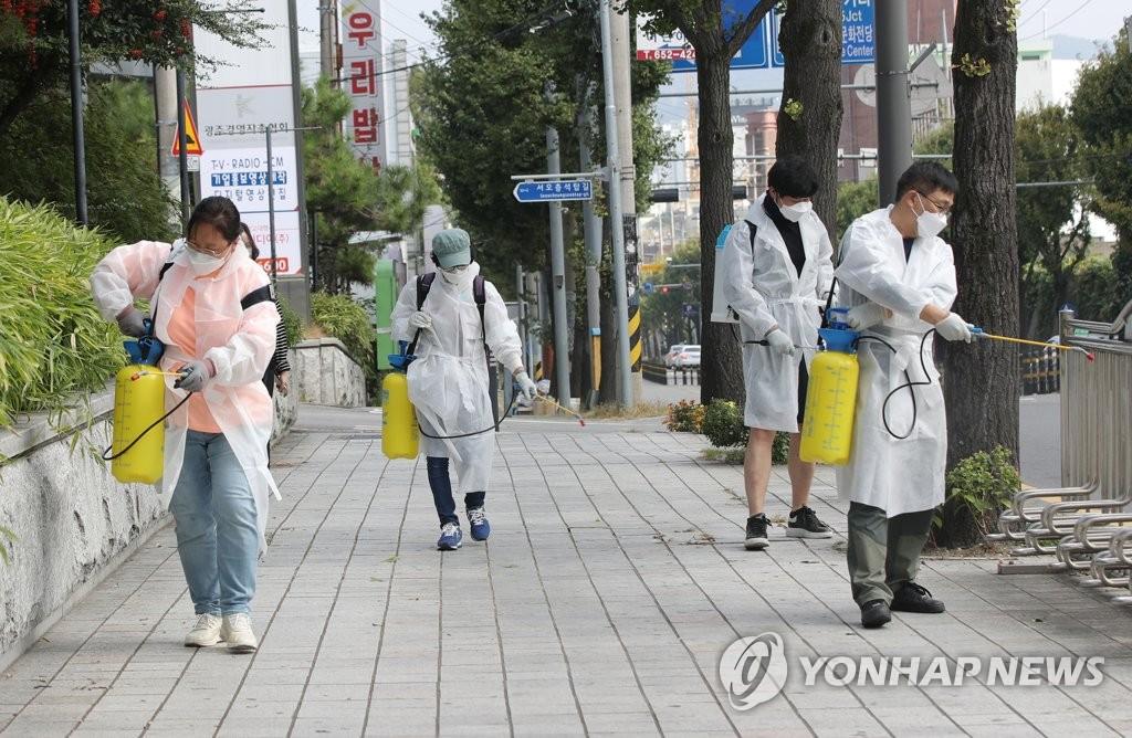 资料图片:10月12日,在光州市南区社稷洞一带,工作人员在街头消毒防疫,防范新冠疫情扩散。 韩联社