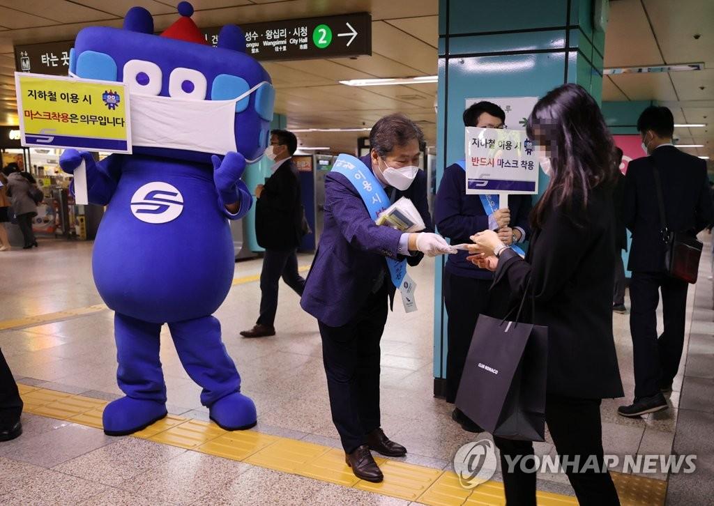 资料图片:10月13日,在首尔蚕室地铁站,首尔交通公社工作人员给市民分发口罩。韩国当天起要求民众在利用公共交通工具和访问医疗机构时必须佩戴口罩,违规者从下月13日起将被处以10万韩元(约合人民币600元)的罚款。 韩联社