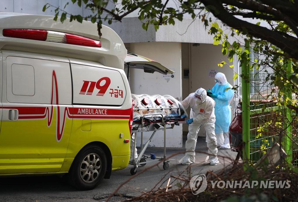 资料图片:防疫人员在移送确诊感染新冠病毒的疗养院患者。 韩联社