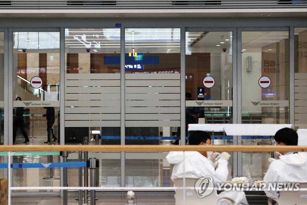 资料图片:防疫人员在机场入境大厅稍事休息。 韩联社