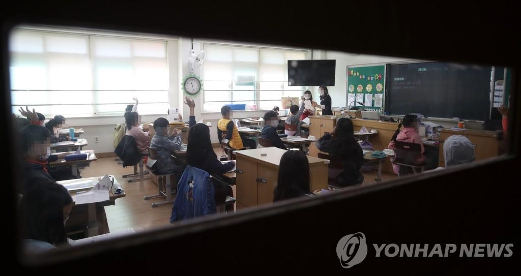 资料图片:在一所小学,学生们戴着口罩上课。 韩联社