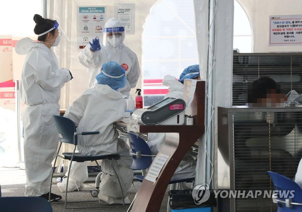资料图片:在一处筛查诊所,防疫人员为进行病毒检测做准备。 韩联社