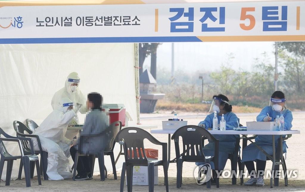 资料图片:在一处筛查诊所,防疫人员针对市民进行病毒检测。 韩联社