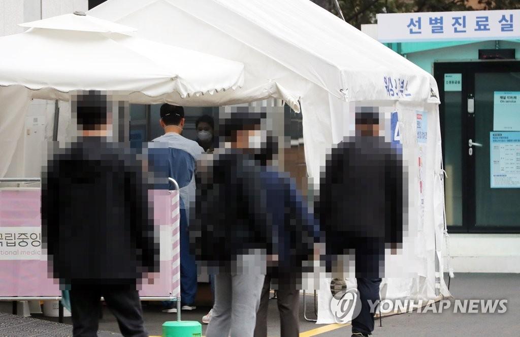 资料图片:民众排队候检。 韩联社