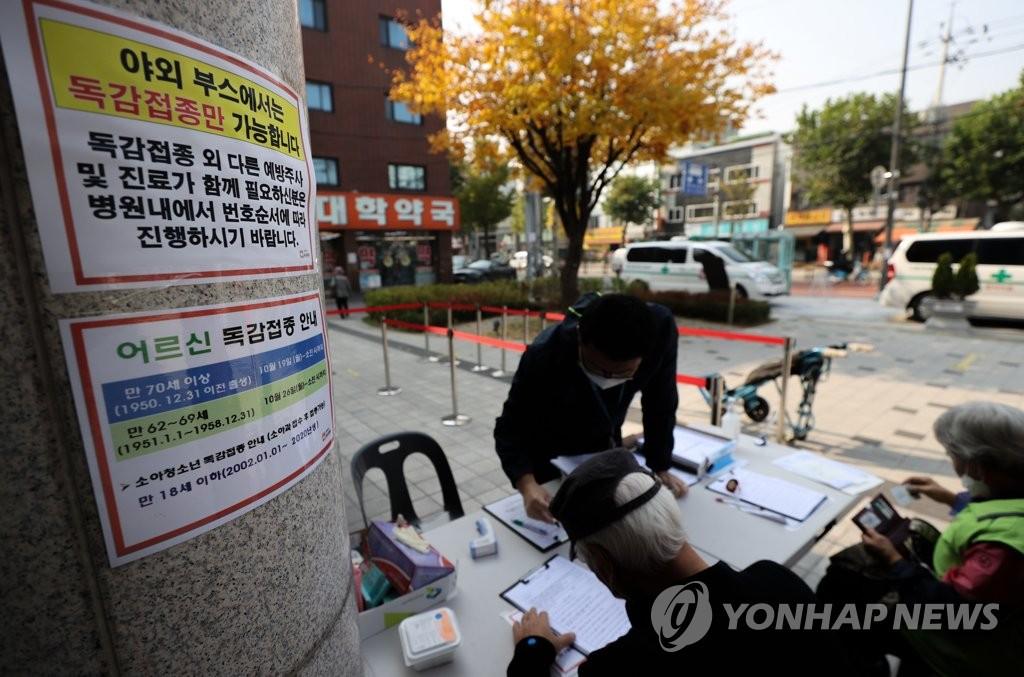 10月27日,在首尔一家医院,市民们在接种流感疫苗前填写问诊表。 韩联社