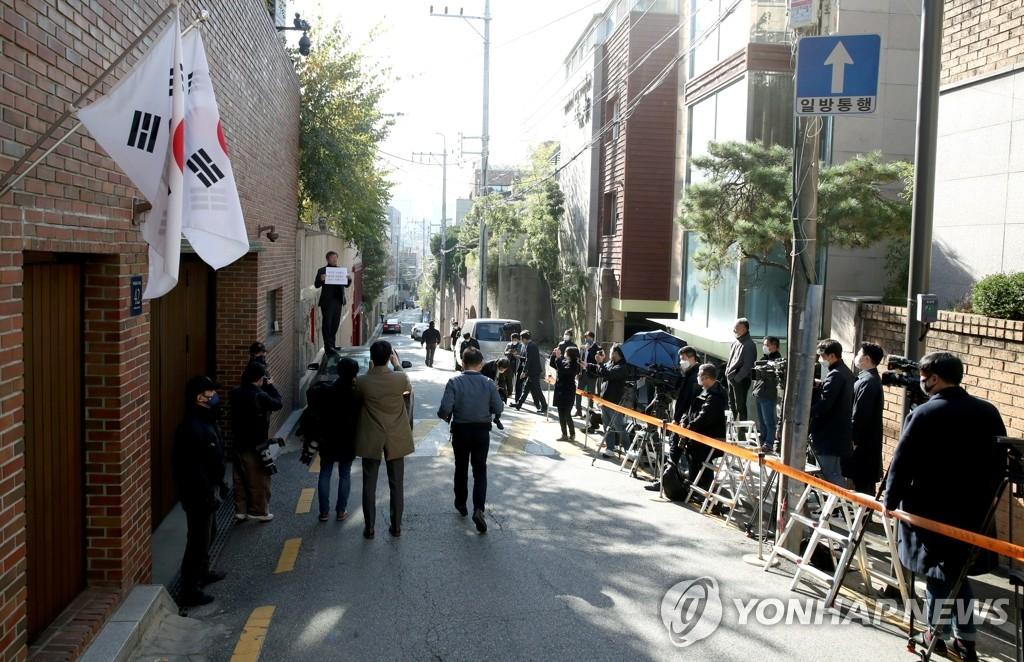 10月29日,在首尔论岘洞的前总统李明博私宅前,媒体记者等待报道。 韩联社