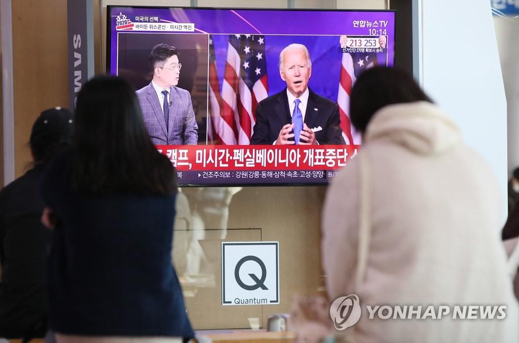 11月5日上午,在首尔站候车大厅,人们正在收看关于美国大选的新闻。 韩联社