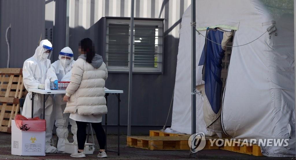 资料图片:市民接受新冠病毒相关问诊。 韩联社