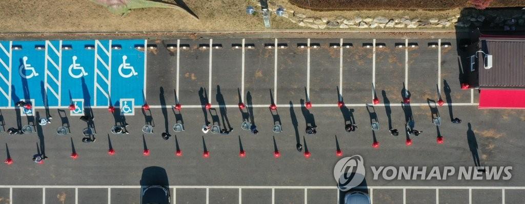 资料图片:市民排起长龙等候接受新冠检测。 韩联社