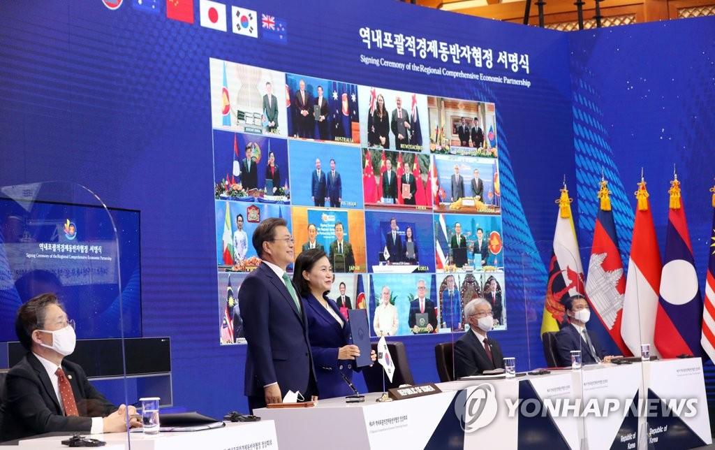 资料图片:2019年11月15日,韩国总统文在寅(左二)出席世界上最大的自由贸易协定——《区域全面经济伙伴关系协定》(RCEP)签字仪式后,同产业通商资源部通商交涉本部长俞明希合影留念。 韩联社
