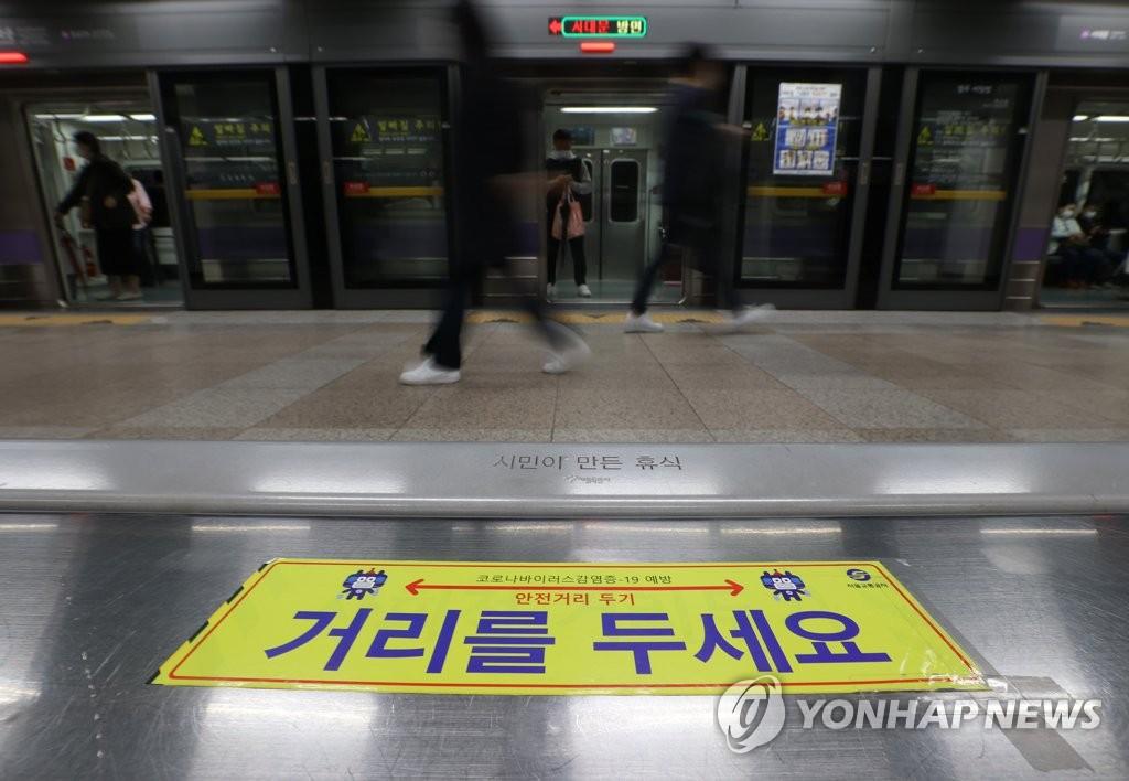 资料图片:11月19日,首尔市光化门地铁站内部贴着宣传保持社交距离的告示。 韩联社