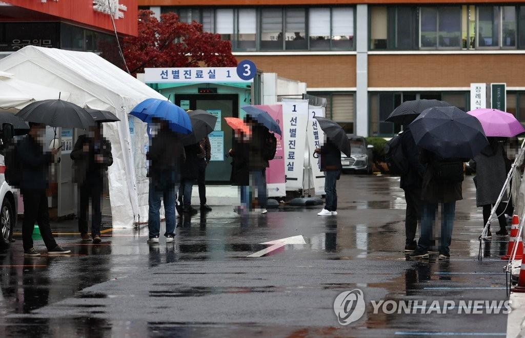 资料图片:市民排队待检。 韩联社