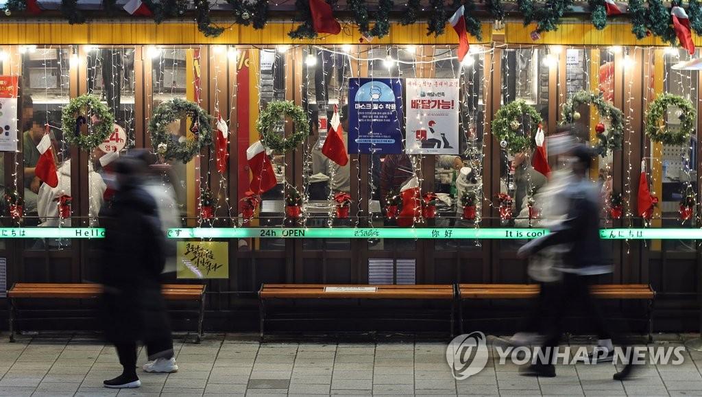 资料图片:年底降至,疫情再度扩散。图为首尔一家餐厅门口,摄于11月19日。 韩联社
