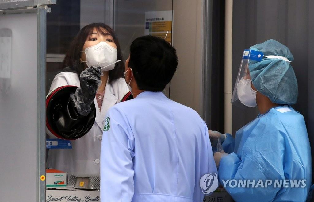 资料图片:医务人员正在接受新冠病毒检测。 韩联社