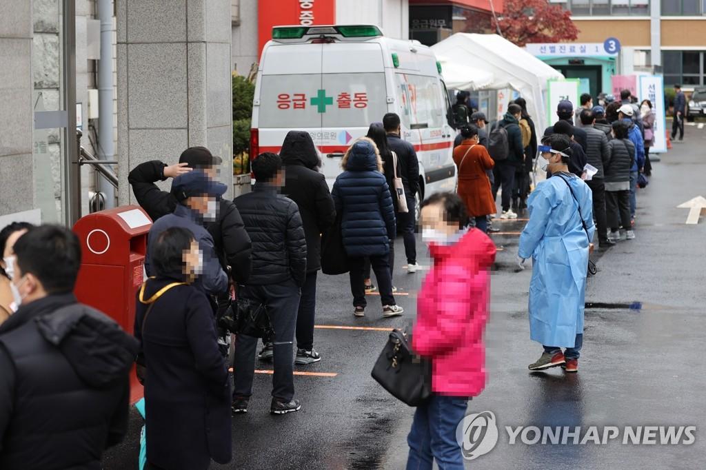 资料图片:市民排队接受新冠病毒检测。 韩联社