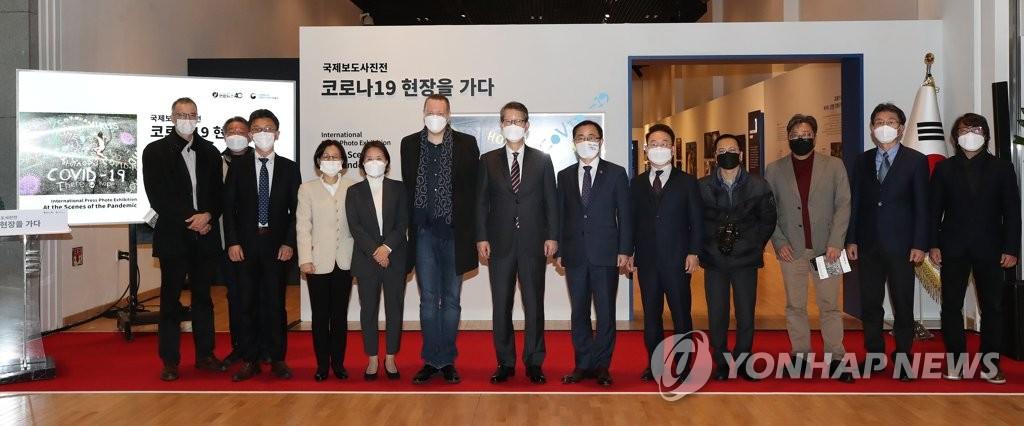 """11月24日,""""国际新闻图片展:直击新冠疫情一线""""在首尔钟路区的大韩民国历史博物馆开幕。图为与会嘉宾合影。 韩联社"""
