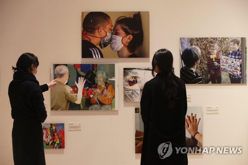 """11月24日,""""国际新闻图片展:直击新冠疫情一线""""在首尔钟路区的大韩民国历史博物馆开幕。图为访客观展。 韩联社"""