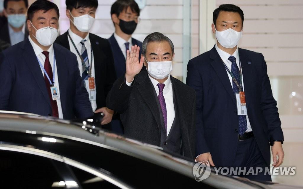 11月25日,在仁川国际机场,中国国务委员兼外交部长王毅向韩国记者挥手致意。 韩联社