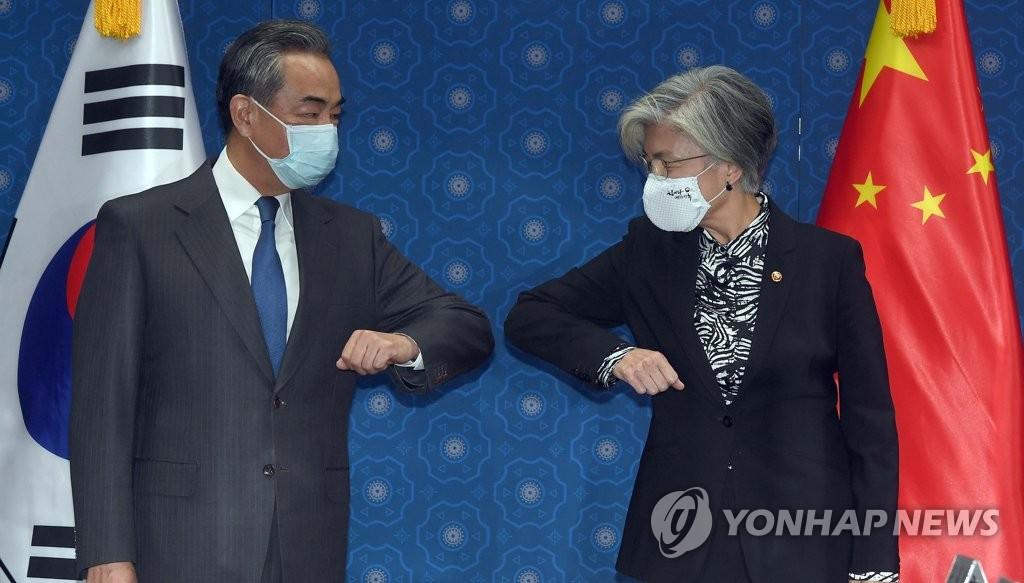 11月26日,在首尔外交部大楼,韩国外交部长官康京和(右)和到访的中国外交部长王毅在会谈开始前碰肘代替握手。 韩联社/联合摄影团