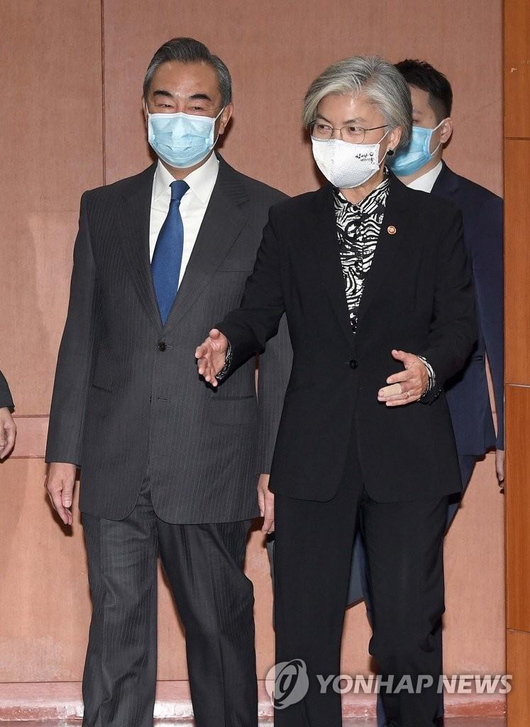 11月26日,在首尔外交部大楼,韩国外交部长官康京和(右)和到访的中国外交部长王毅走向会场。 韩联社/联合摄影团