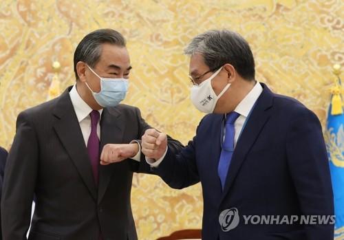 王毅和韩幕僚长碰肘致意