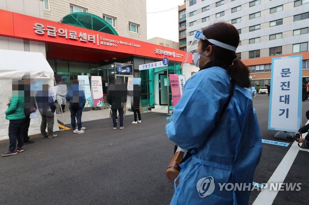 资料图片:在一处筛查诊所,防疫人员监视为接受病毒检测排队的市民。 韩联社