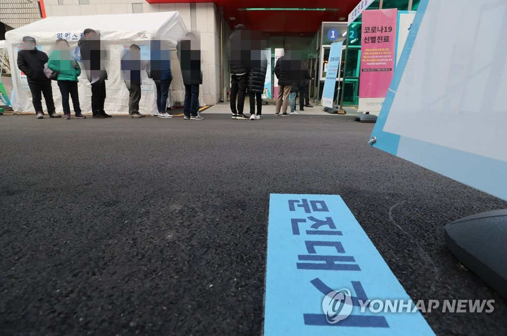 资料图片:11月27日,在首尔中区一处筛查诊所,人们排长队候检。 韩联社