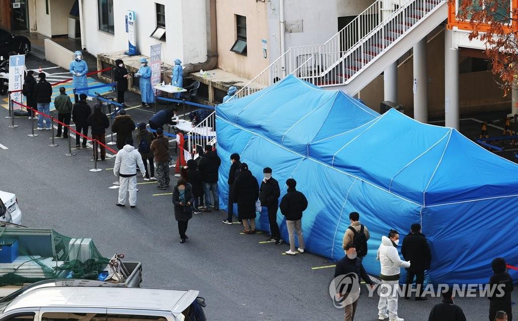 资料图片:筛查诊所前候检人员排长龙。 韩联社