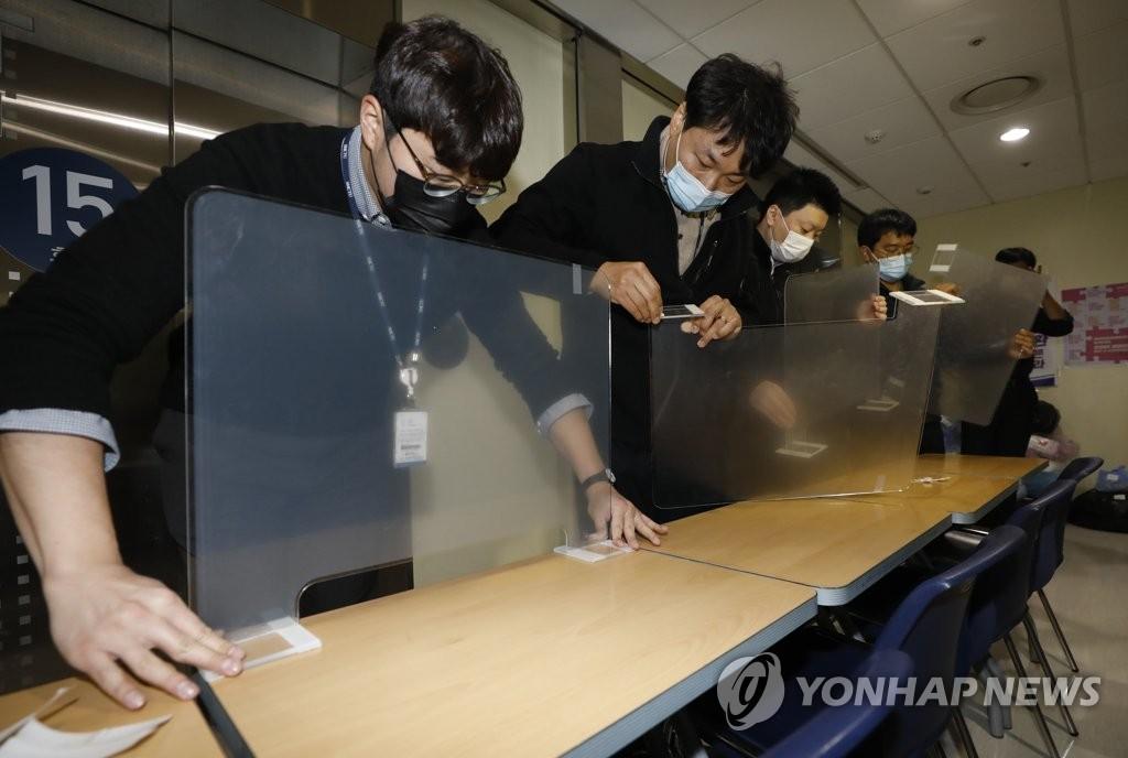 资料图片:防疫人员在高考场内桌子上设置隔板。 韩联社