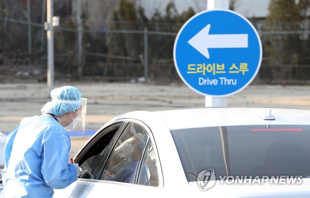 """资料图片:12月7日下午,在首尔市龙山区顺天乡大学医院,医务人员指引候检者接受""""免下车""""核酸检测采样服务。 韩联社"""