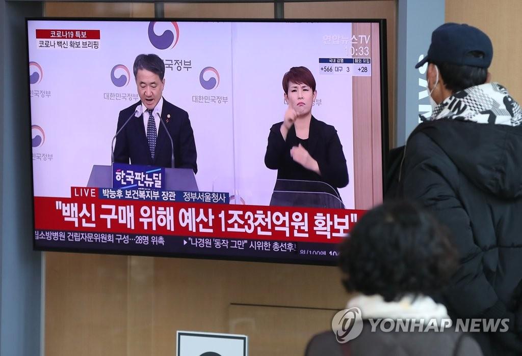 资料图片:12月8日,在首尔火车站,民众正在收看政府新冠疫苗采购计划记者会直播。韩国保健福祉部当天表示,政府总共确保4400万剂疫苗,可供88%的韩国人口接种。 韩联社